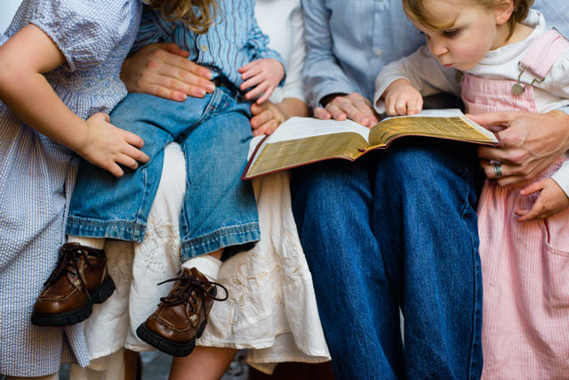 Parents reading Bible to children